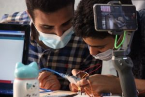 two LYBOTICS participants work on a circuitboard