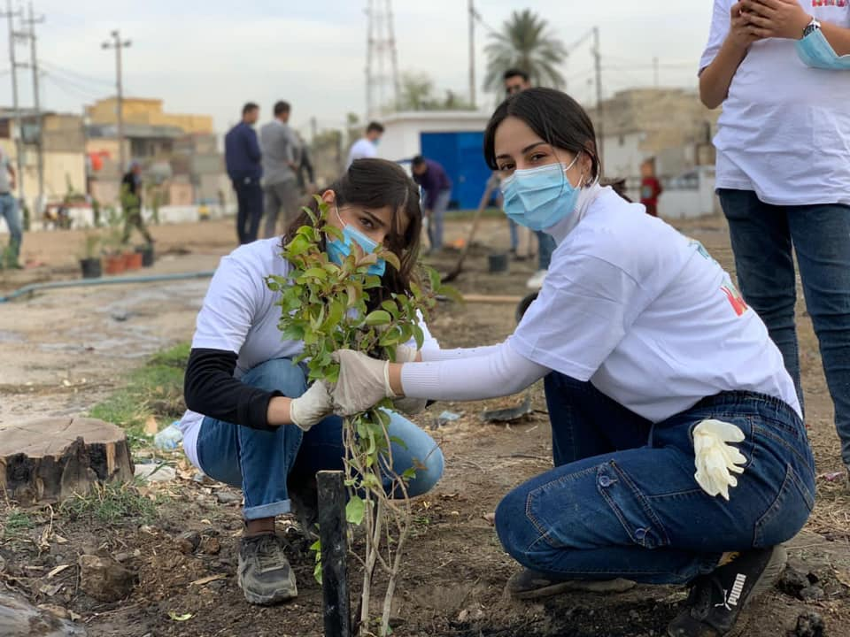two girls plant a tree during a Better World Organization event